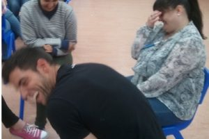 a man turns away in hysterical laughter and his colleagues are laughing during a play exercise in a Play Skills for Staff workshop