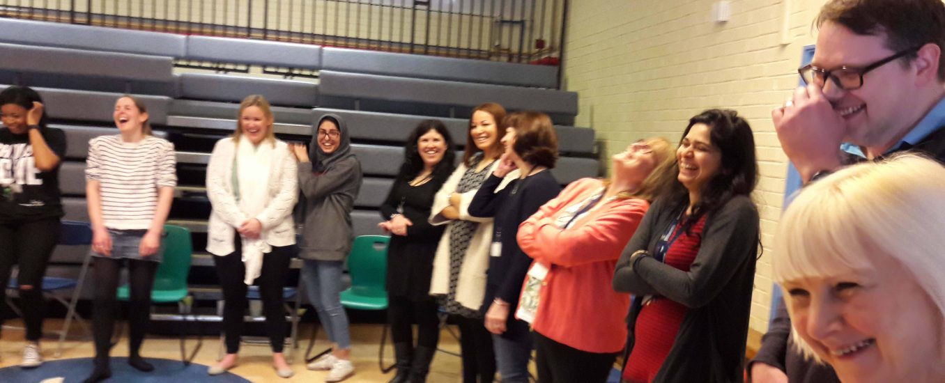 Teachers in a line all in the middle of laughing together during a wellbeing at work INSET for teachers and school staff using laughter and play