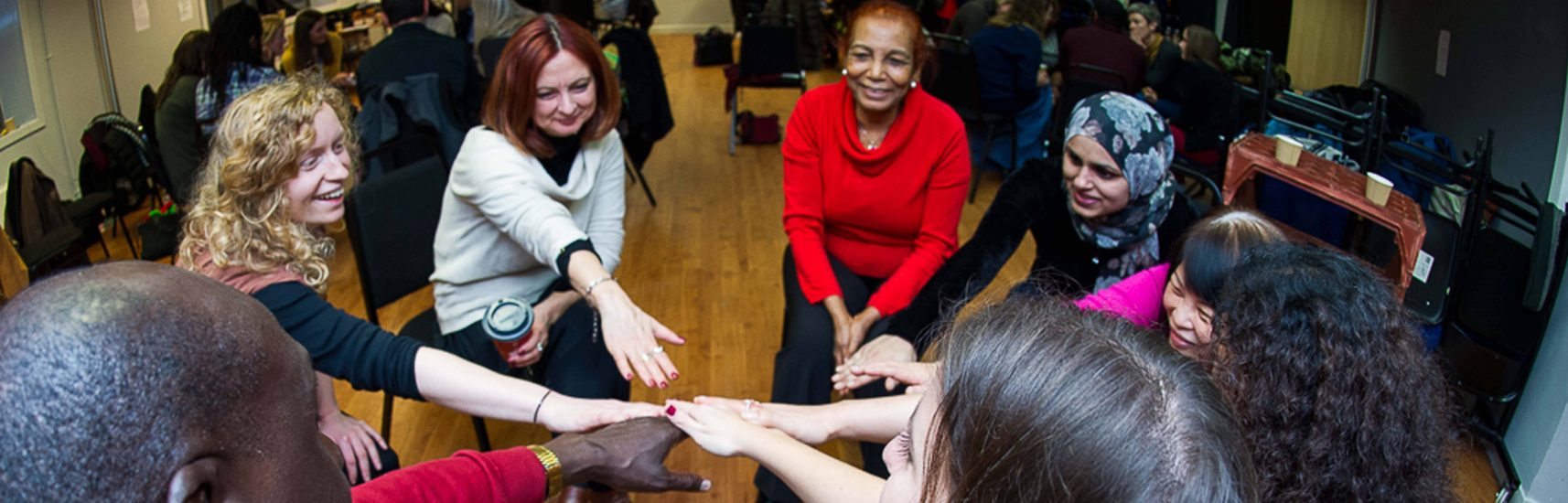A group of colleagues reaching into a circle so that their hands touch in the middle duing a team building london activity