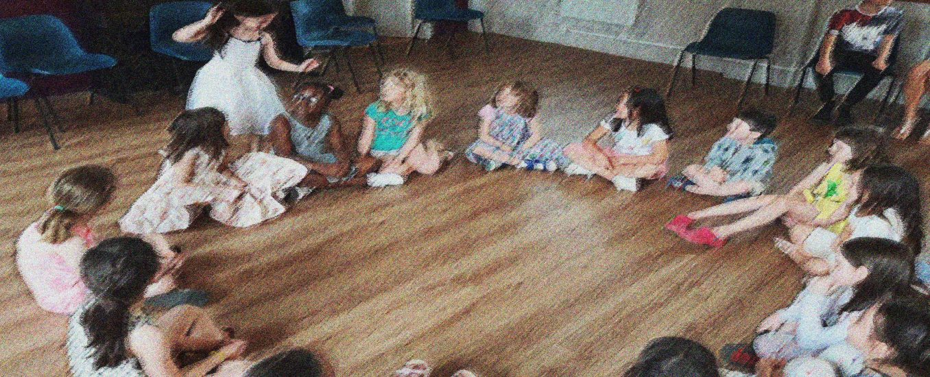 A group of children sitting in a circle one is going round the outside in a game of Duck Duck Goose at one of our Life and Social Skills play workshops for children