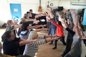 Two lines of staff facing each other waving their arms and laughing during a play skills for staff workshop