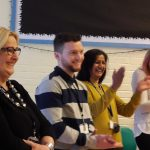 Four teachers laughing and one is mid clap as they laugh with one another during INSET for staff wellbeing