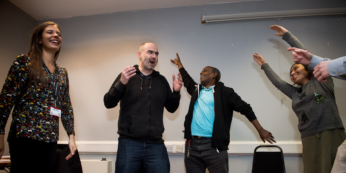People laughing and expressing themselves stretching arms and playing at a creative team building London workshop