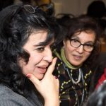 Close up of a woman's face as she looks and listens to someone and the person beside her is also looking and listening during a presentation skills activity