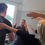 People stretch their arms as they play at a workshop for adults in their home