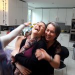 A woman roars with laughter with her friend during a game at a play workshop for parties