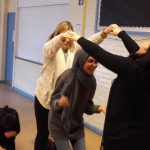 Two women make a bridge whilst their colleage is smiling and ducking during a play skills workshop