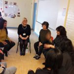 A group of teachers sit in a circle playing a mime game at their INSET workshop they are laughing
