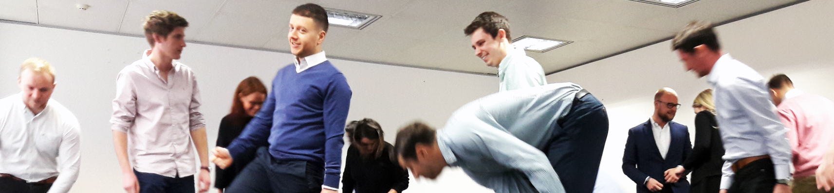 Corporate team doing silly walks as part of a team building workshop in London