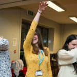 Three women playing with their arms in funny poses during a staff wellbeing and team building London workshop