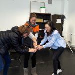 Three women link hands and lean towards each other smiling during a game at a play workshop for adults