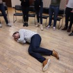 A man lies on the floor smiling and the feet of his colleagues make a circle around him during a playful workshop for adults