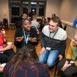 People engaged in talking and laughing in groups during a wellbeing at work event