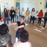 A teacher stretches her arms out towards a colleague as they play during an INSET workshop