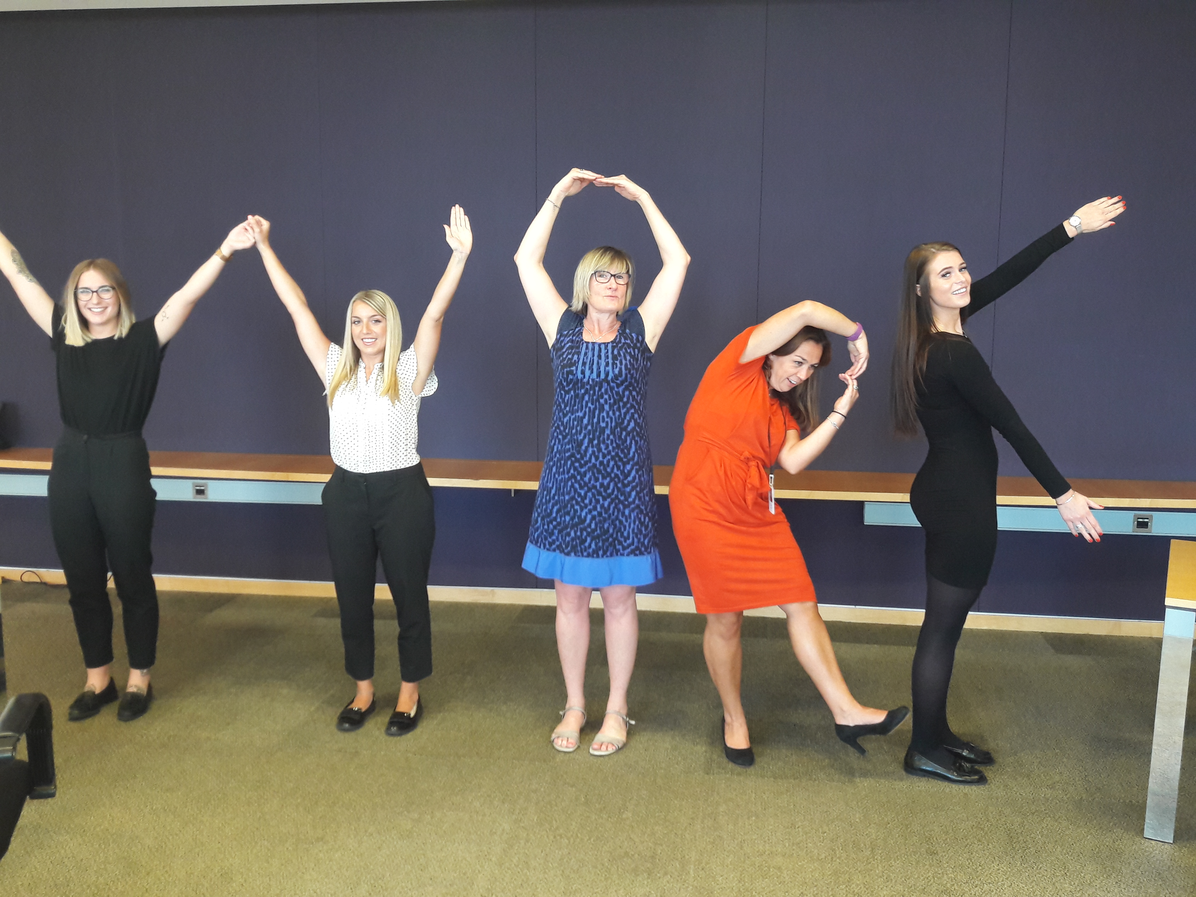 "Women spelling out the word ""work"" as part of a team building london excercise"